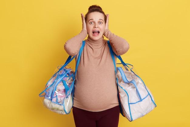 Frustrierte schwangere frau, die mit verrücktem ausdruck schreit, fühlt panik, bedeckt ohren und weit geöffneten mund isoliert über gelber wand.