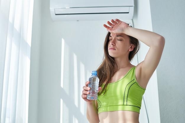 Frustrierte schwitzende frau, die unter hitze, durst und heißem wetter leidet, kühlt mit klimaanlage und kalter erfrischender wasserflasche ab.