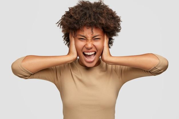 Frustrierte stressige schwarze dame bedeckt ohren mit beiden händen, runzelt die stirn