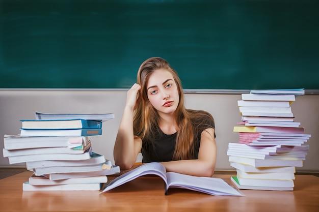 Frustrierte studentin, die am schreibtisch mit einem enormen stapel von studienbüchern im klassenzimmer sitzt.