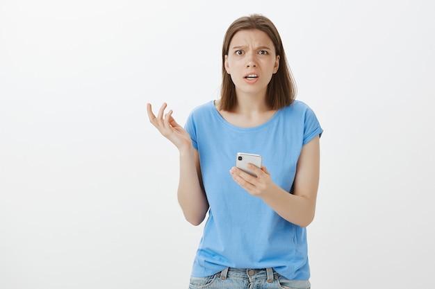 Frustrierte und gestörte frau, die verwirrt auf smartphonebildschirm schaut