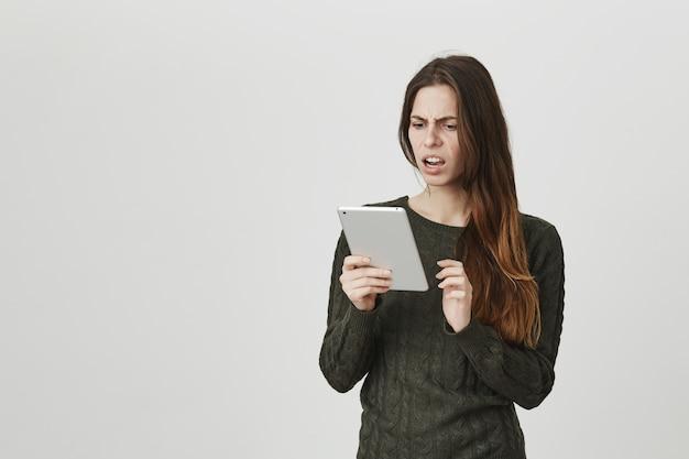 Frustrierte und schockierte junge frau, die digitalen tablettbildschirm betrachtet
