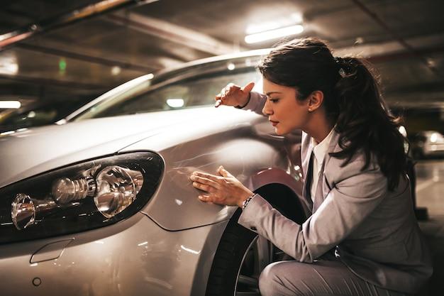 Frustrierte und verängstigte junge geschäftsfrau, die ihr zerkratztes auto betrachtet.