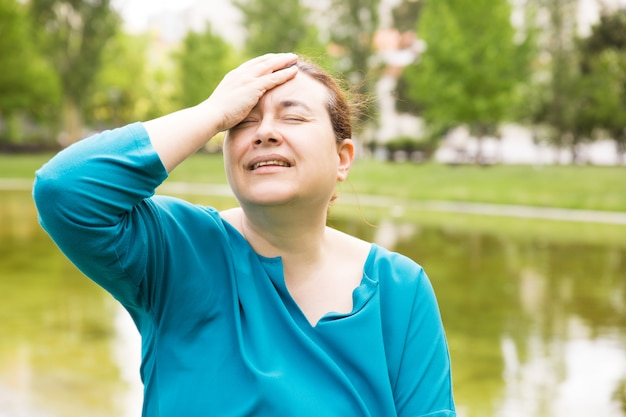 Frustrierte unglückliche frau, die unter kopfschmerzen leidet