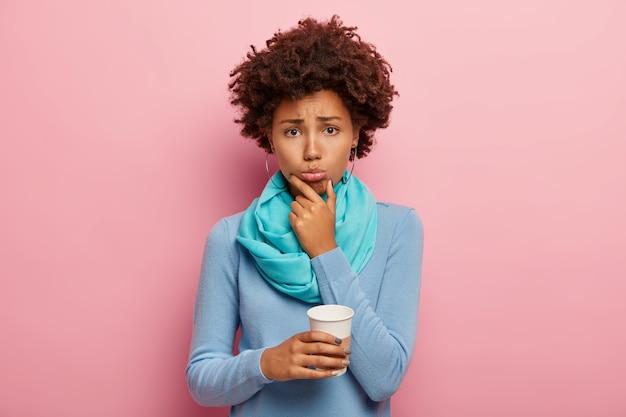 Frustrierte unglückliche frau hält kaffee zum mitnehmen, versucht das problem zu lösen, ist überarbeitet, hält das kinn und sieht traurig aus