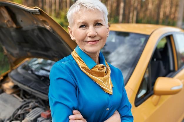 Frustrierte unglückliche rentnerin, die mit offener motorhaube neben ihrem auto steht, die arme verschränkt hält und auf pannenhilfe wartet.