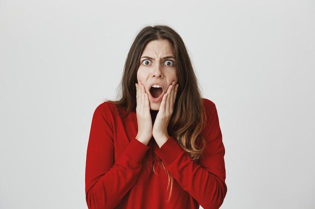 Frustrierte verrückte frau hören schlechte nachrichten, keuchen und starren wütend