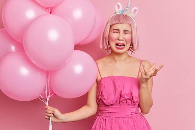 Frustrierte weinende asiatische frau mit rosa bob-haar hebt hand hat traurigen gesichtsausdruck verärgert wegen urlaubsfeier allein