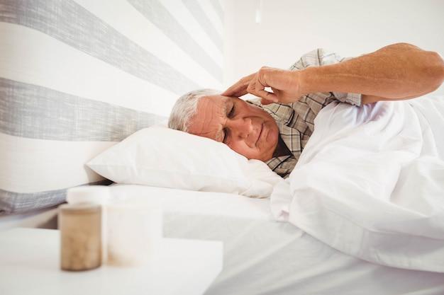 Frustrierter älterer mann, der auf bett im schlafzimmer liegt