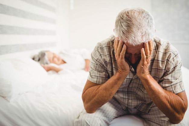 Frustrierter älterer mann, der auf bett im schlafzimmer sitzt