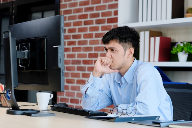 Frustrierter asiatischer geschäftsmann, der computer beim arbeiten im büro betrachtet