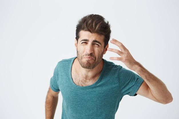 Frustrierter attraktiver bärtiger kaukasischer typ im trendigen blauen t-shirt, mit mürrischem verrückten ausdruck, der mit der hand gestikuliert. menschliche mimik und emotionen.