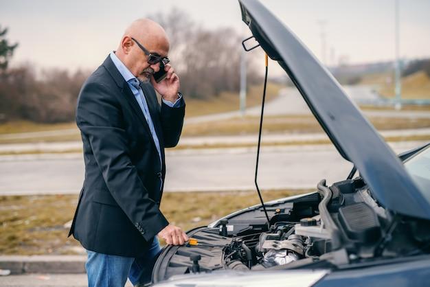 Frustrierter bärtiger älterer erwachsener mann, der autoservice anruft, während er vor geöffneter motorhaube seines autos steht.