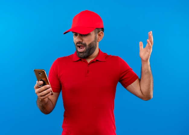 Frustrierter bärtiger lieferbote in der roten uniform und in der kappe, die den arm des smartphones hält, der unzufrieden ist, über blauer wand stehend