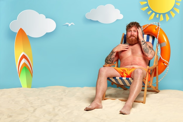 Frustrierter bärtiger rothaariger mann bekommt am strand einen sonnenbrand