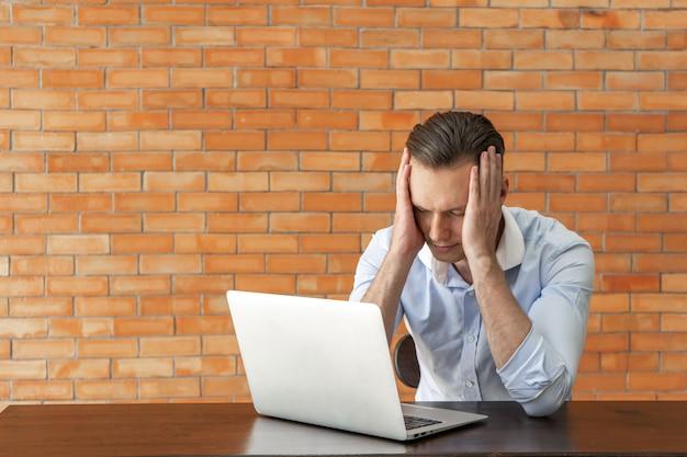Frustrierter geschäftsmann, der an laptop mit backsteinmauer arbeitet