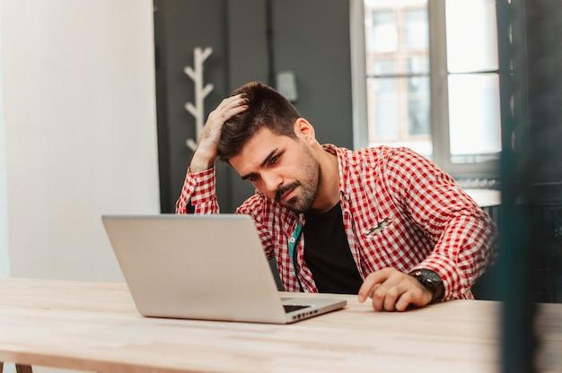 Frustrierter geschäftsmann, der auf schreibtisch mit der hand auf kopf im büro sitzt.