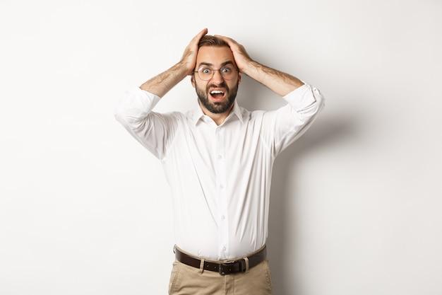 Frustrierter geschäftsmann, der hände auf kopf hält, schockiert und ängstlich aussieht und steht