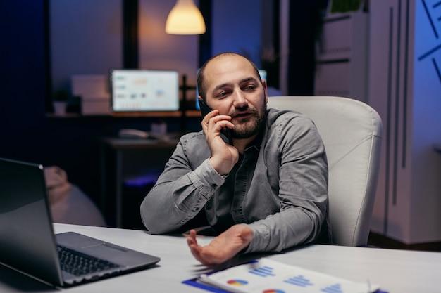 Frustrierter geschäftsmann, der spät im büro arbeitet und am telefon spricht, um aufgaben zu erledigen. manager, der ein geschäftsgespräch mit smartphone führt, während er überstunden im büro macht.
