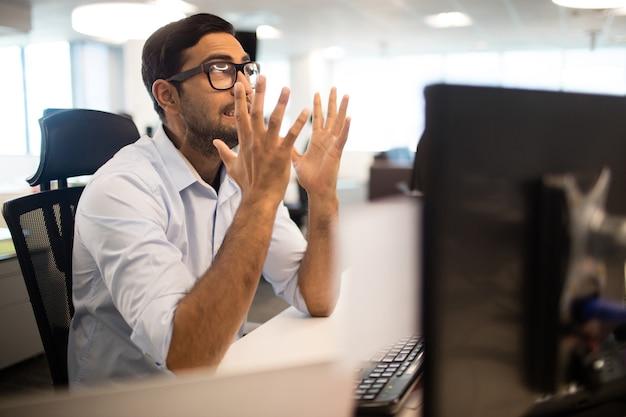 Frustrierter geschäftsmann, der zähne im büro zusammenbeißt
