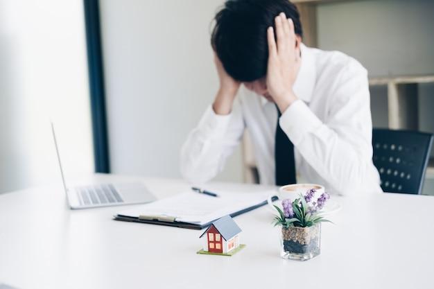 Frustrierter geschäftsmanndruck, wenn mit immobilienmaklerarbeit beim sitzen am schreibtisch versagen