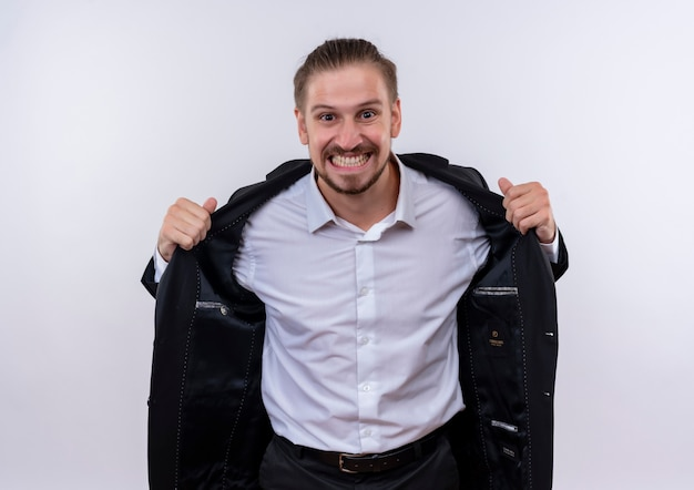 Frustrierter hübscher geschäftsmann, der anzug trägt, der kamera betrachtet, die wild geht, indem er seinen anzug abnimmt, der über weißem hintergrund steht