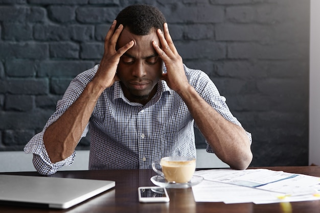 Frustrierter junger afroamerikanischer geschäftsmann, der starke kopfschmerzen hat