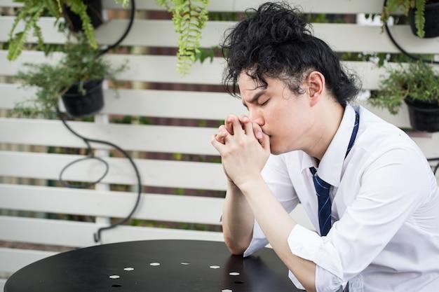Frustrierter junger asiatischer geschäftsmann fiel aus, um sich hoffnungslos zu fühlen, ausfallendes konzept des geschäftsproblems