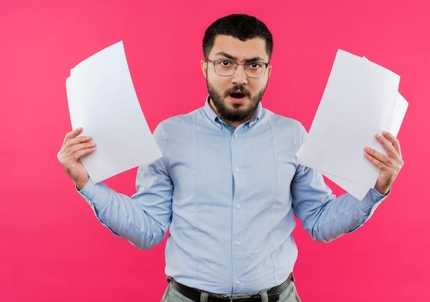 Frustrierter junger bärtiger mann in der brille und im blauen hemd, die leere seiten mit wütendem gesicht halten