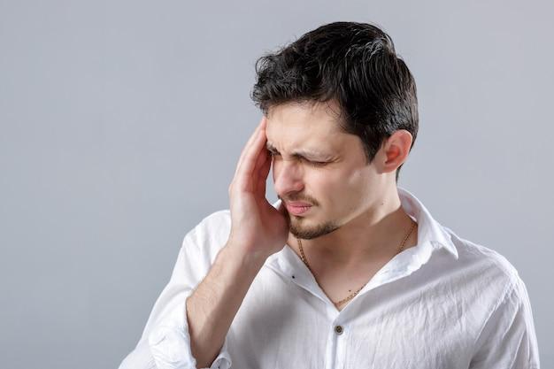 Frustrierter junger brünette mann in einem weißen hemd mit kopfschmerzen auf grauem hintergrund. schreckliche migräne