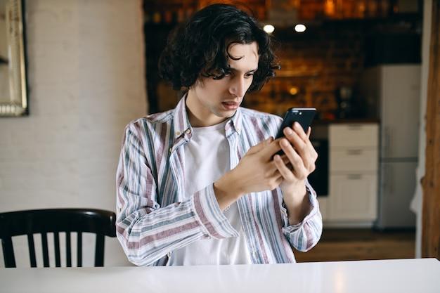 Frustrierter junger mann, der schlechte nachrichten beim surfen im internet auf dem handy liest. besorgter schüler kann nicht telefonieren, weil er das guthaben aufladen muss.