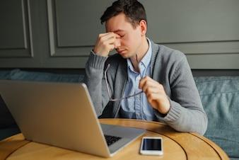 Frustrierter junger Mann, der seine Nase massiert und Augen beim Arbeiten geschlossen hält