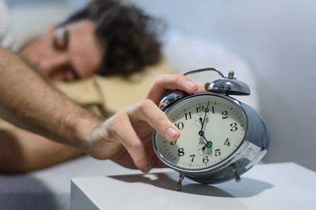 Frustrierter junger mann geweckt durch seinen wecker