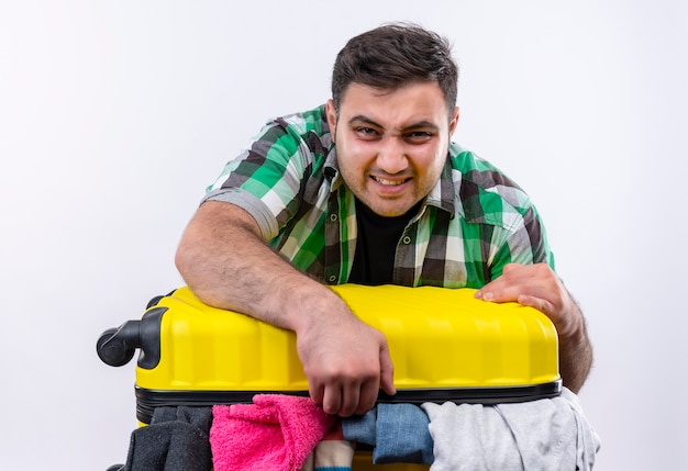 Frustrierter junger reisender mann im karierten hemd stehend mit koffer voller kleidung, der versucht, es mit wütendem gesicht über weißer wand zu schließen