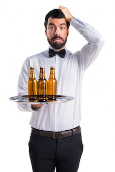Frustrierter kellner mit bierflaschen auf dem tablett
