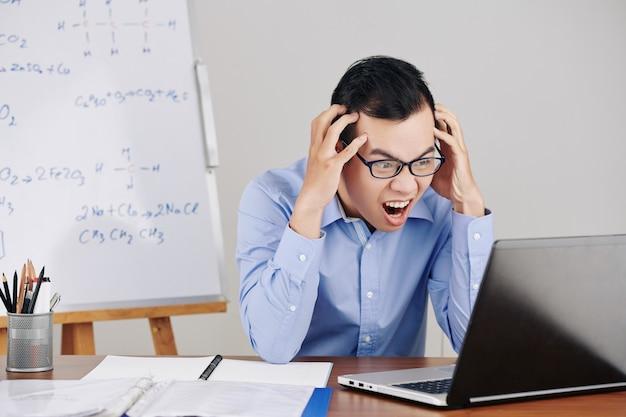 Frustrierter lehrer, der geöffneten laptop betrachtet