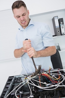 Frustrierter mann, der hammer verwendet, um drähte von cpu herauszuziehen