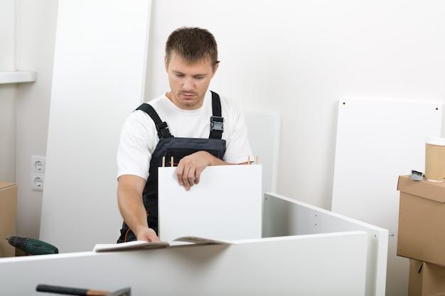 Frustrierter mann, gekleidet in die allgemeine leseanweisung der arbeiter und das zusammenstellen von selbstmontagemöbeln. diy, heim- und umzugskonzept