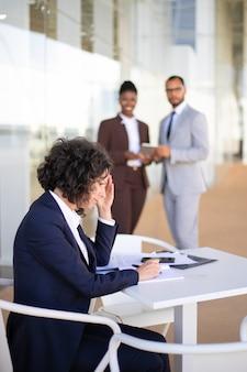 Frustrierter müder weiblicher angestellter, der mit dokumenten arbeitet