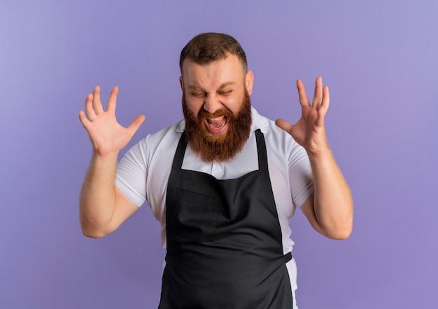 Frustrierter professioneller bärtiger friseurmann in der schürze, der mit aggressivem ausdruck mit erhobenen armen über lila wand schreit