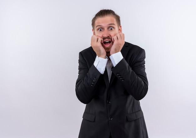 Frustrierter schöner geschäftsmann, der anzug trug, schockierte blick auf kamera, die über weißem hintergrund steht