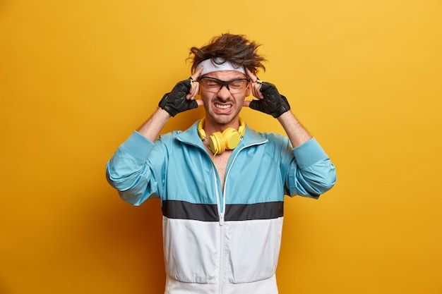 Frustrierter sportler verspürt nach dem training unerträgliche kopfschmerzen, hält die schläfen in den händen, beißt die zähne zusammen, konzentriert sich auf die aufgabe, trägt sporthandschuhe und aktive kleidung und leidet unter migräne. müder kranker sportlicher typ