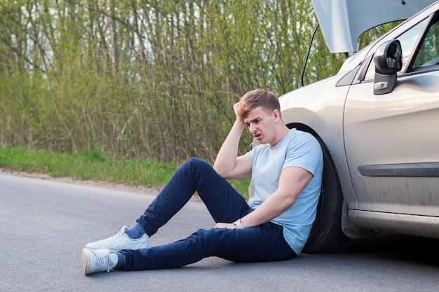 Frustrierter trauriger verärgerter kerlfahrer sitzt in der nähe eines kaputten autos nach verkehrsunfall, unfall. der junge, schockierte, verzweifelte, verängstigte mann geriet in einen verkehrsunfall und saß mit der hand auf asphalt und hielt den kopf