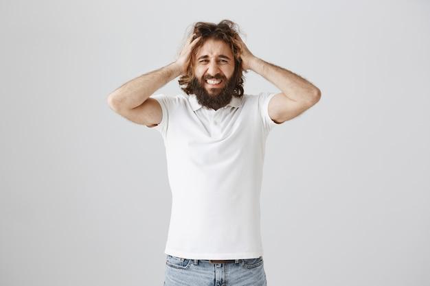 Frustrierter und ängstlicher mann hält hände auf dem kopf und verzieht das gesicht