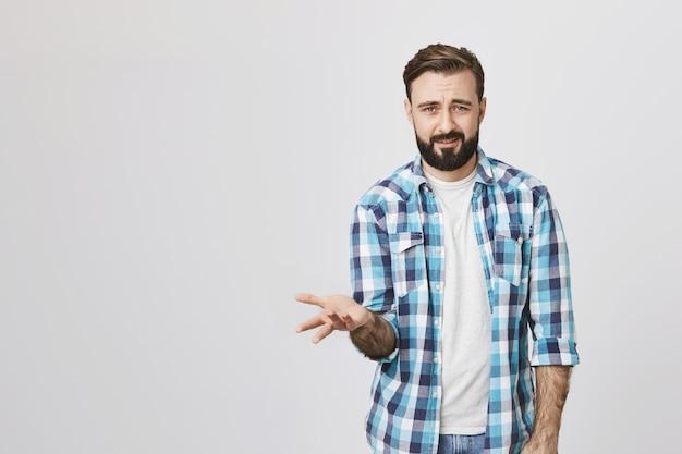 Frustrierter und verwirrter bärtiger mann zuckt die achseln