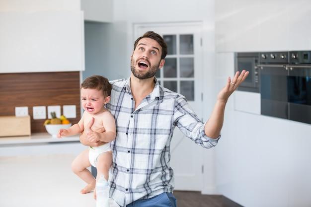 Frustrierter vater, der schreiendes baby in der küche hält
