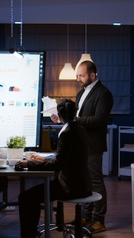 Frustrierter wütender geschäftsmann, der schreit, während er im besprechungsraum des unternehmens überstunden macht, irritiert...