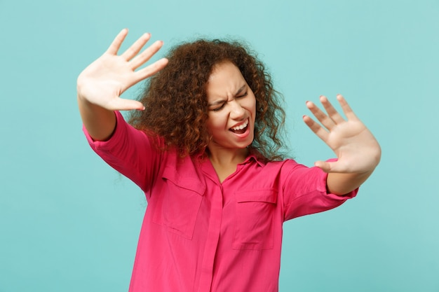 Frustriertes afrikanisches mädchen, das mit ausgestreckten händen steht und stoppgeste mit handflächen zeigt, die auf blau-türkisem wandhintergrund isoliert sind. menschen aufrichtige emotionen, lifestyle-konzept. kopieren sie platz.
