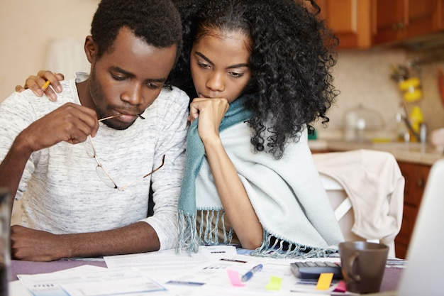 Frustriertes junges afrikanisches paar, das große probleme hat, stromrechnungen zu bezahlen