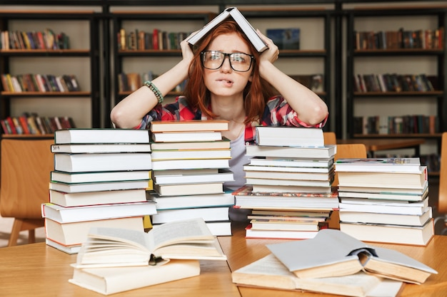 Frustriertes junges mädchen, das an der bibliothek sitzt